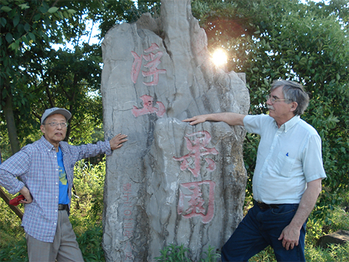 """Translator Zhang Ziqing and myself at the entrance to """"Floating Mountain Tea Farm."""""""
